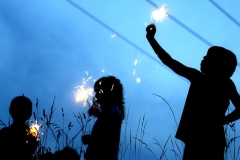 (L-R) Joshua Stoudinger (3), Taylor Holland (4), and Brent Holland (6) play with sparklers before the fireworks begin.
