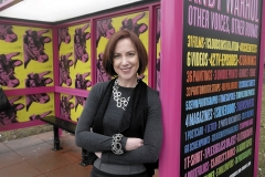 "Even COTA caught Warhol fever: Wexner Center artistic director Sherry Geldin stands next to a bus stop that was decorated in honor of the soon-to-close exhibition ""Andy Warhol: Other Voices, Other Rooms""