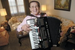 Al Cecutti demonstrates his accordian at his home in Northwest Columbus.